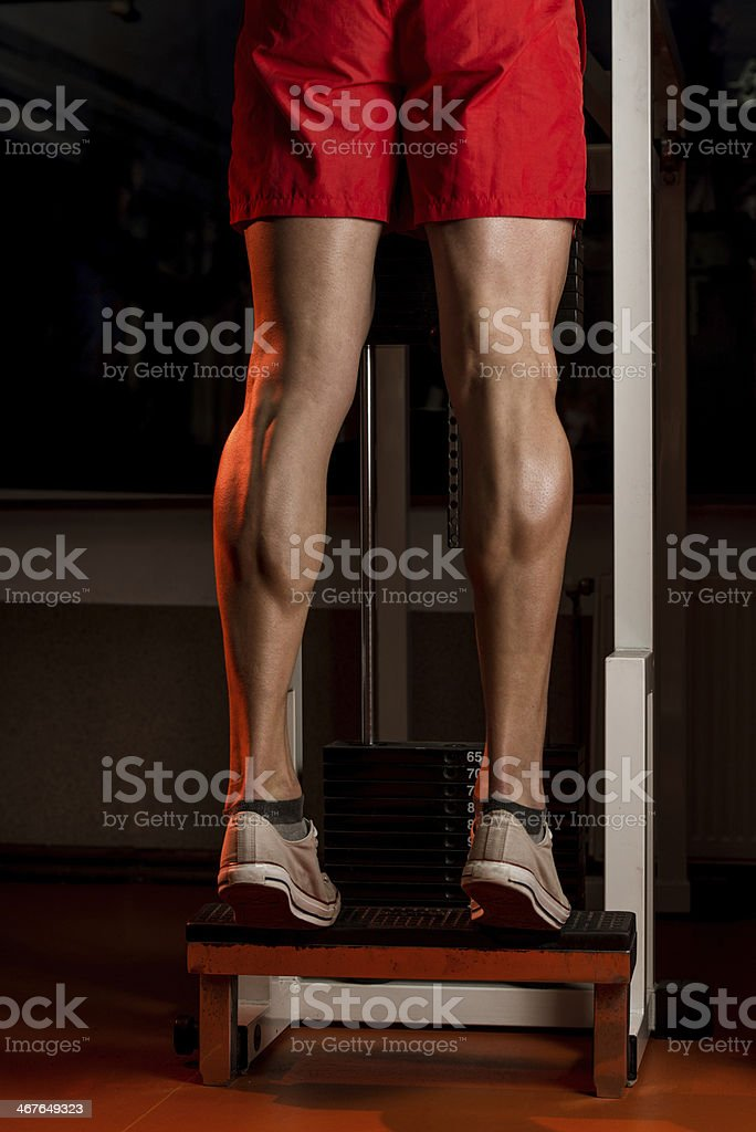Muscular defined male legs on step board stock photo