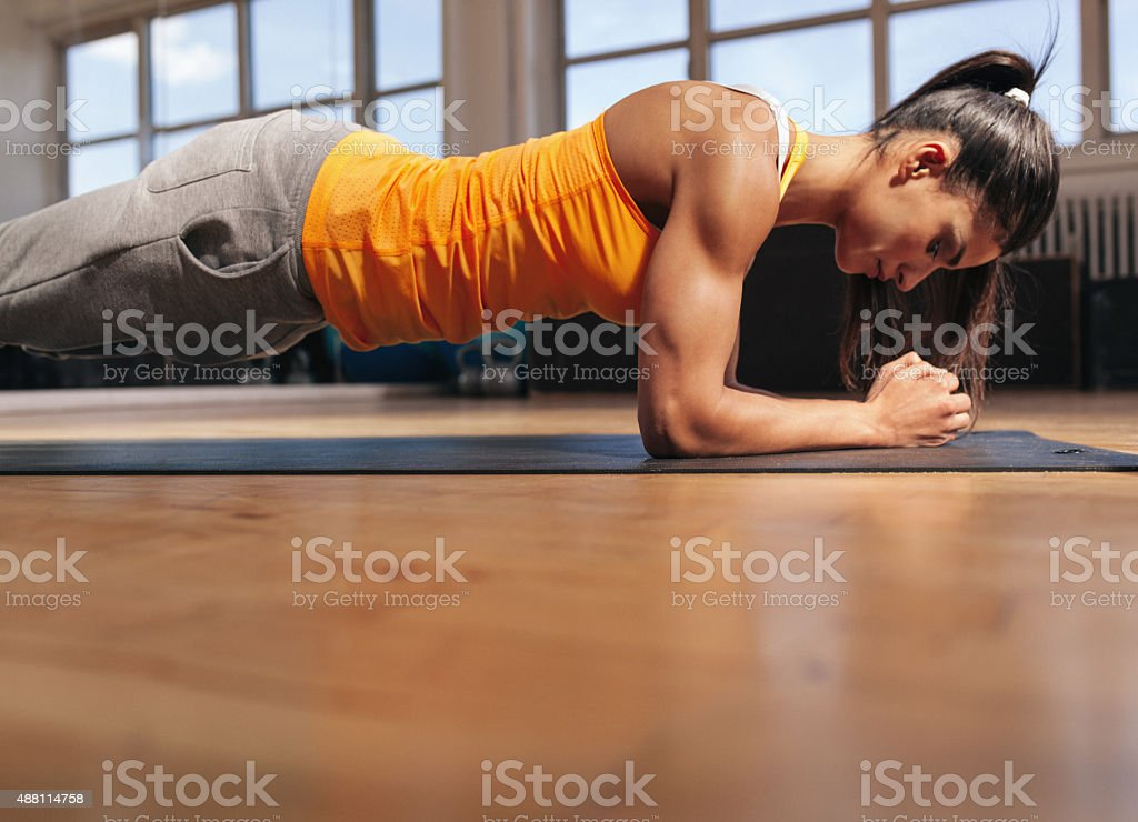 Muscular female doing core workout in the gym stock photo