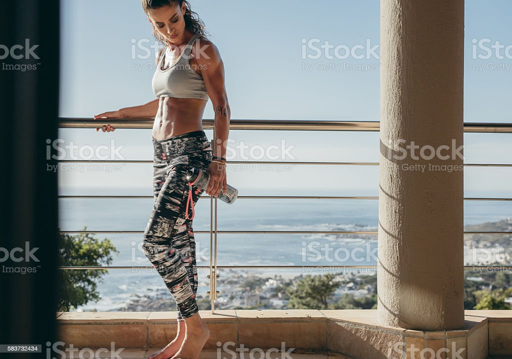 Muscular female in balcony with water bottle stock photo