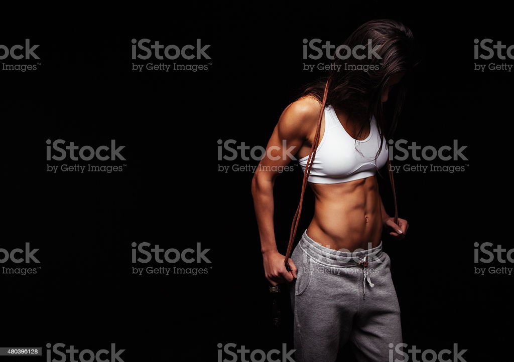 Muscular female posing with jump rope stock photo