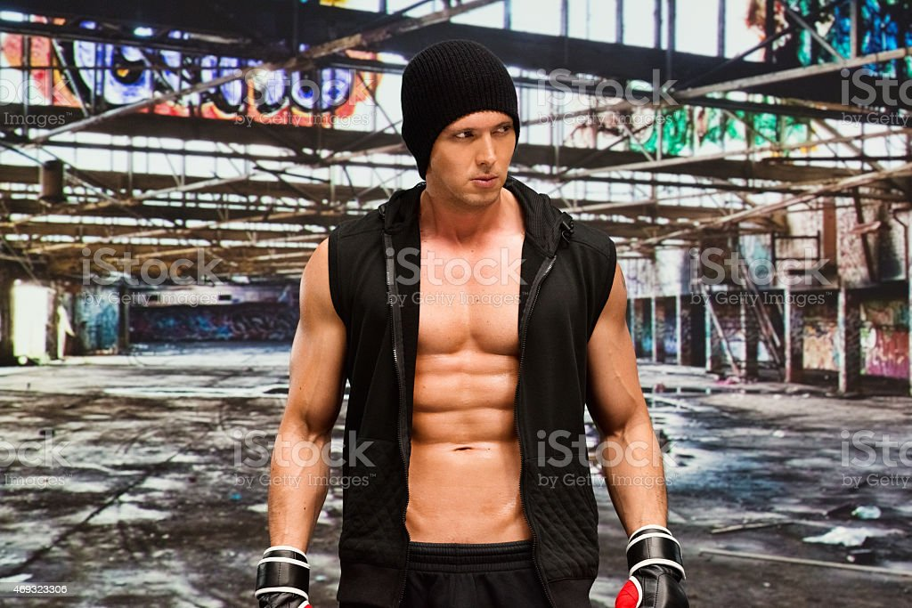 Muscular fighter at the warehouse stock photo