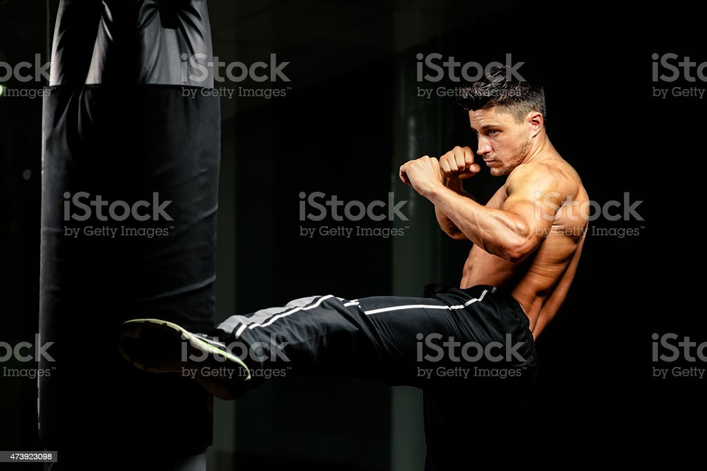 muscular fighter leg middle kick to heavy bag stock photo