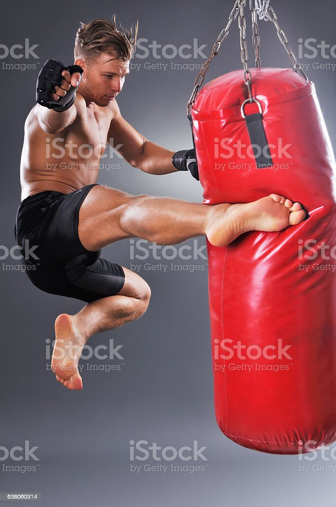 Muscular Fighter Practicing Some Kicks with Punching Bag stock photo