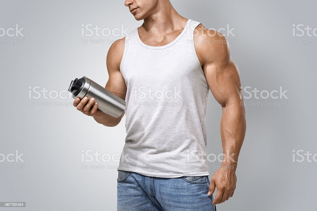 Muscular fitness male holding protein shake bottle stock photo