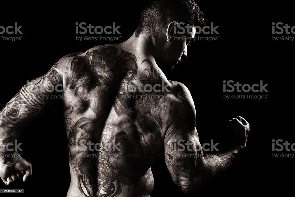 Muscular, Fully Tatooed Male Back Flexing stock photo