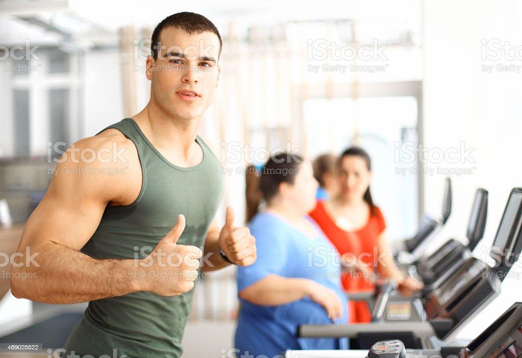 Muscular guy exercising on treadmill. stock photo