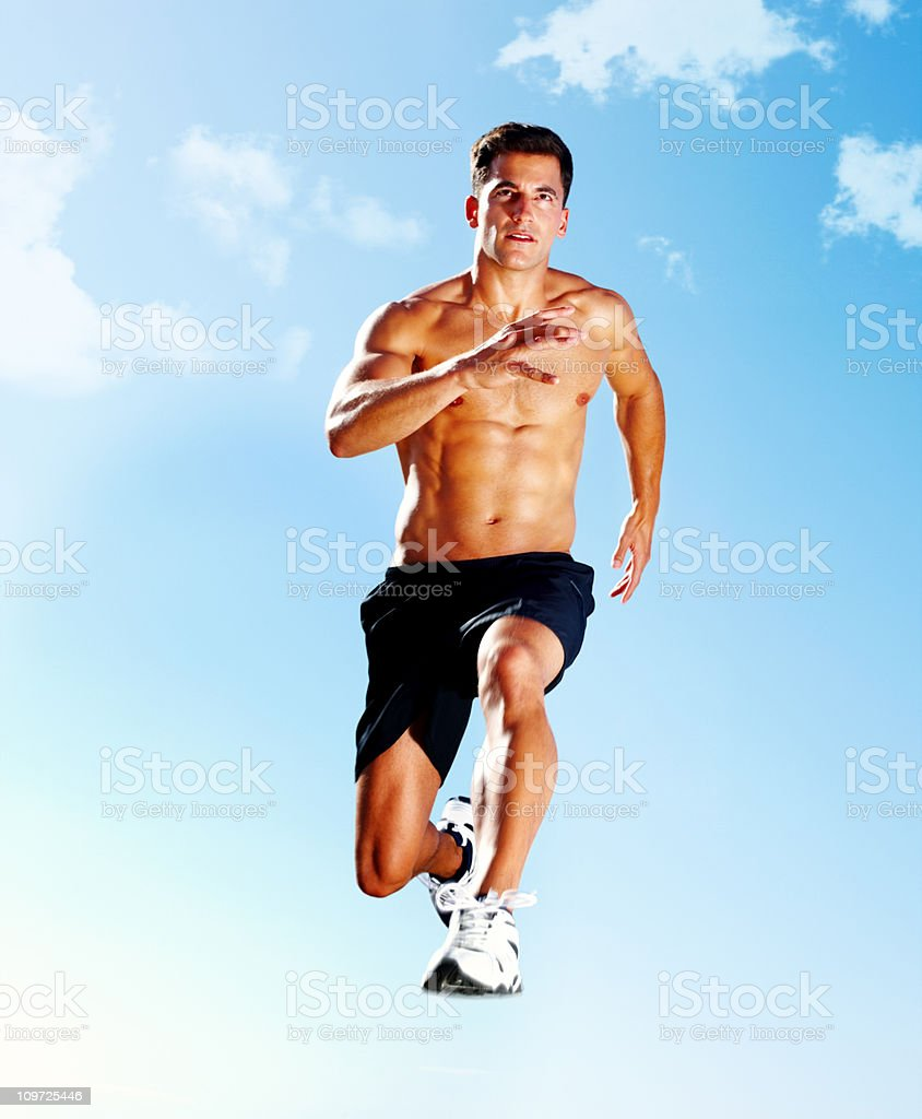 Muscular guy jumping mid-air against sky royalty-free stock photo