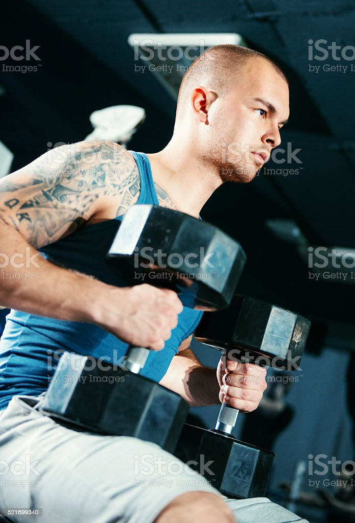 Muscular guy lifting heavy weight for biceps and torso muscles stock photo