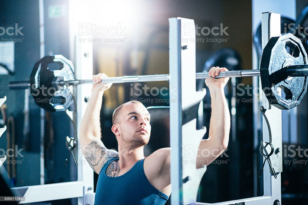 Muscular guy lifting heavy weight for shoulders and torso muscles stock photo