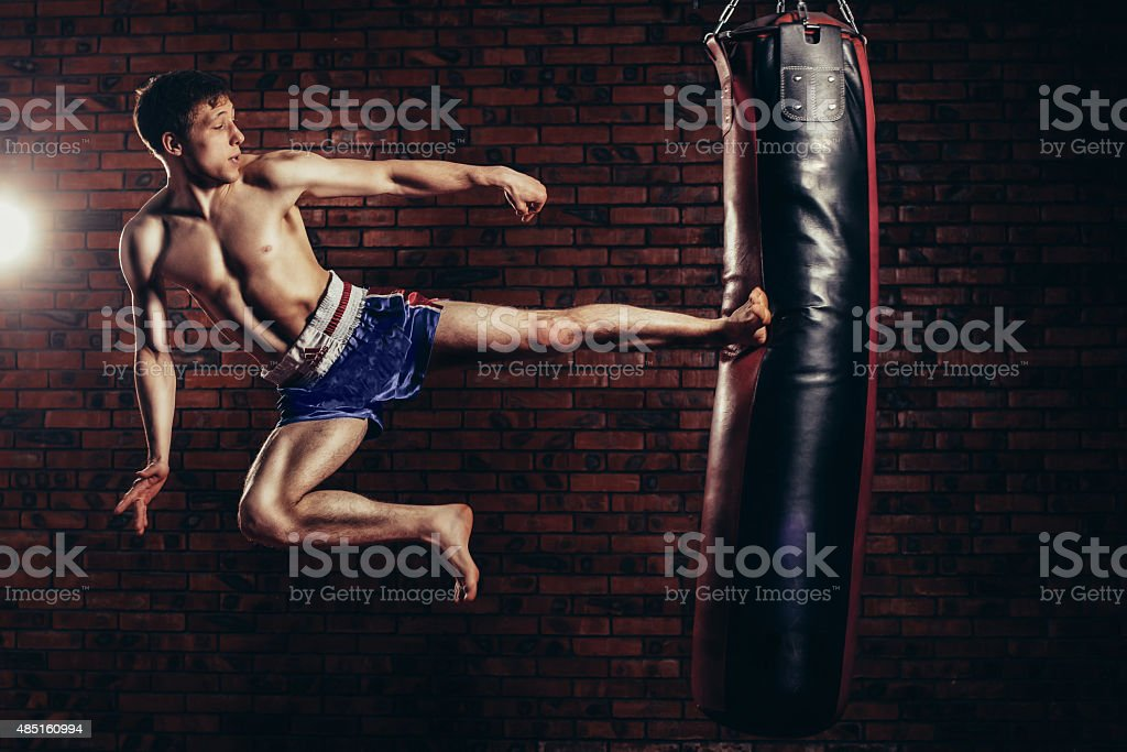 muscular handsome fighter giving a forceful forward kick during  practise stock photo