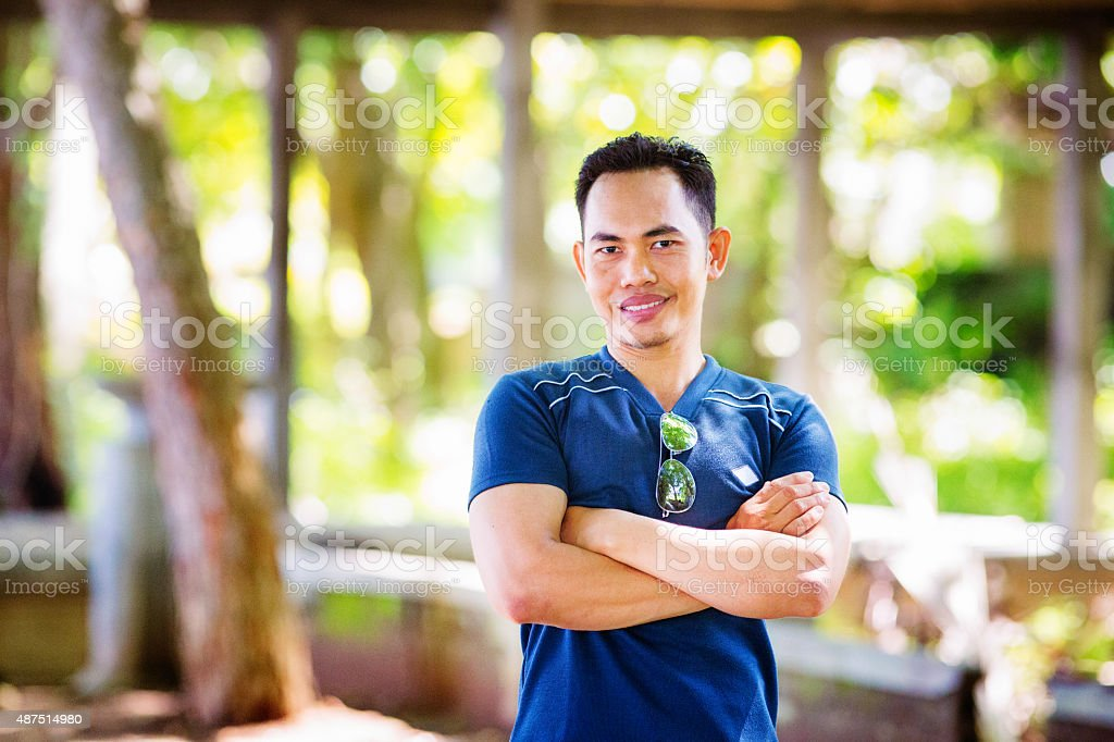 Muscular Indonesian man outdoors portrait arms crossed stock photo
