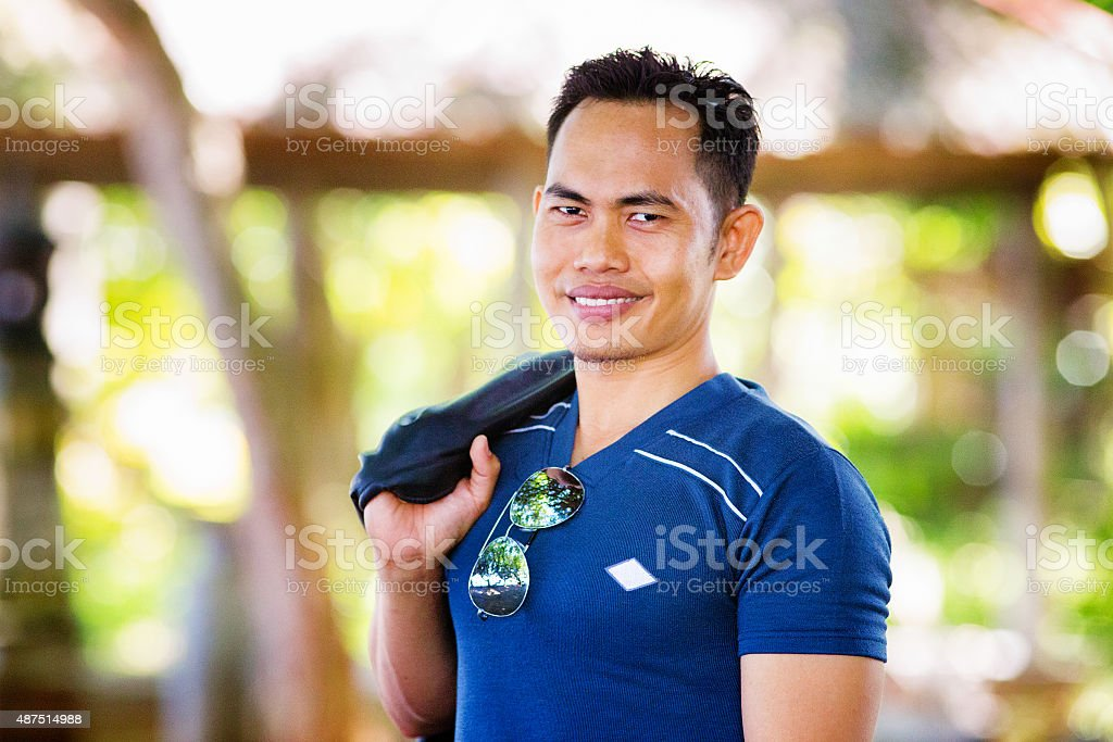 Muscular Indonesian man outdoors portrait holding leather jacket stock photo