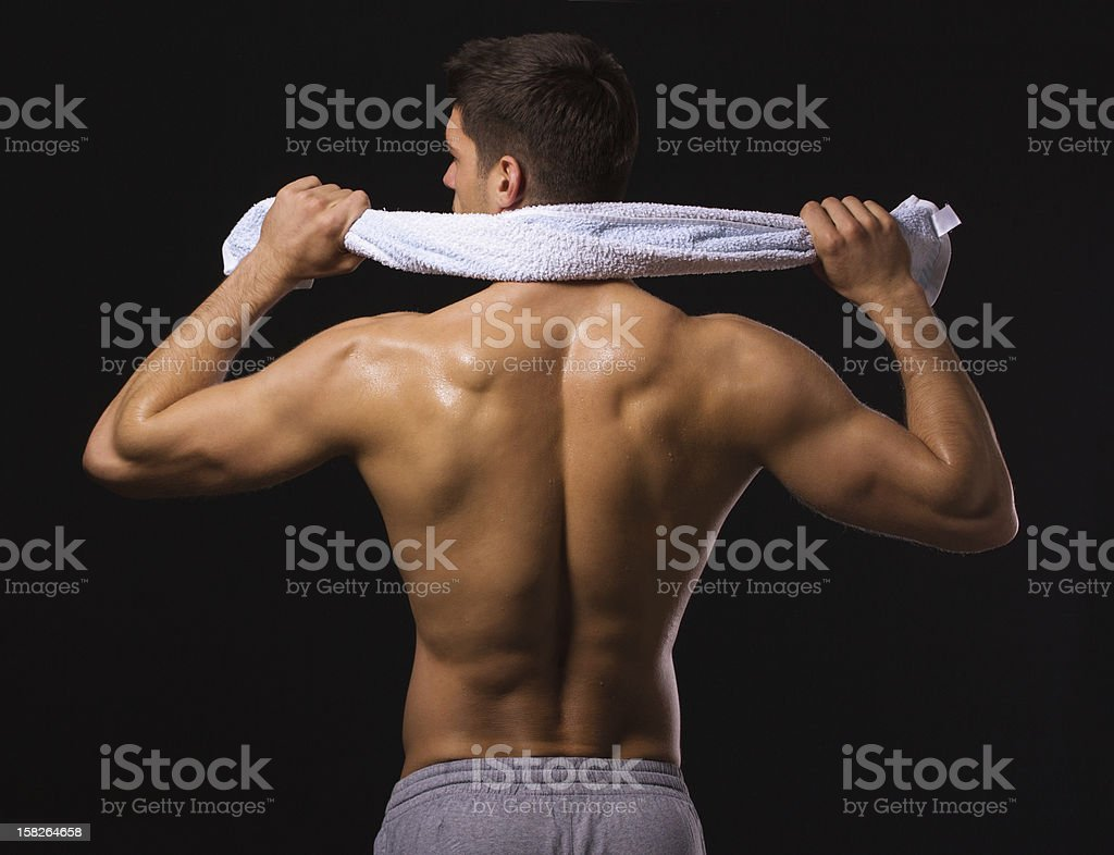 Muscular male back, shirtless man from the behind with towel royalty-free stock photo