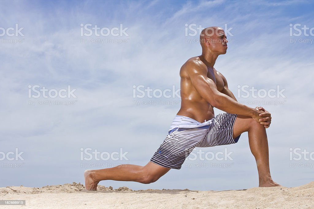 Muscular male doing lunge or stretch on beach no shirt royalty-free stock photo