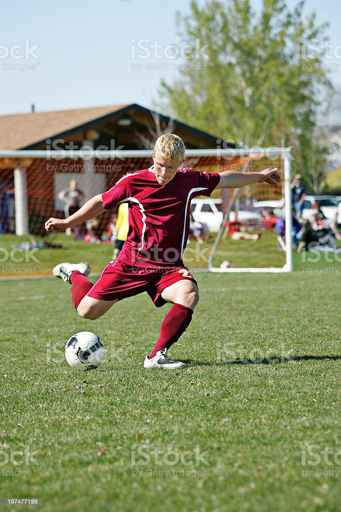 Muscular Male Soccer Player Plants Foot for Determined Power Kick royalty-free stock photo
