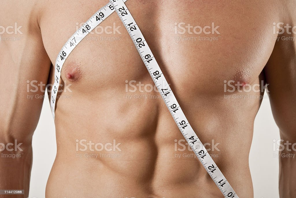 Muscular Male torso draped with tape measure royalty-free stock photo