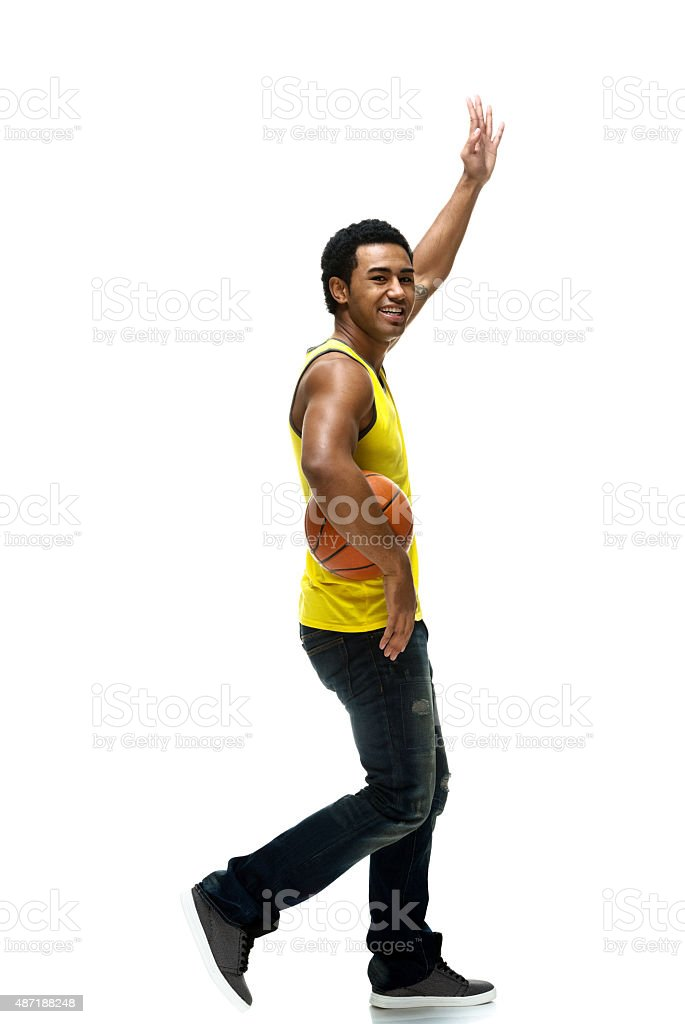 Muscular male waving hand and walking stock photo