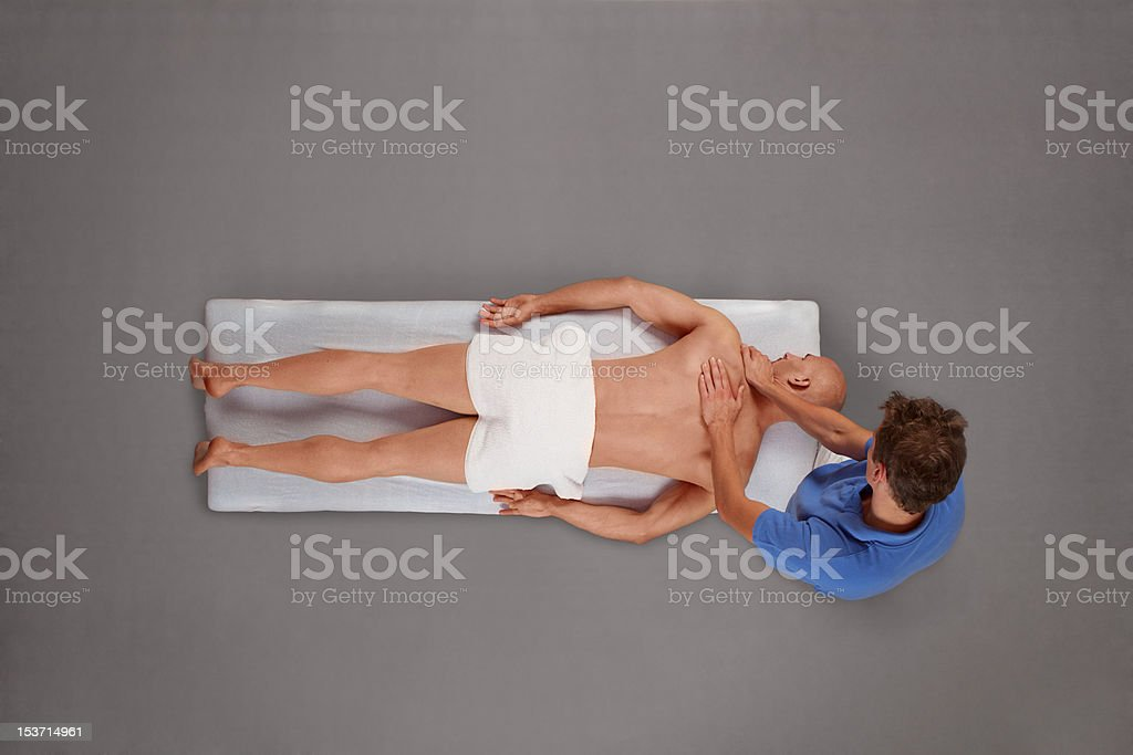 Muscular man being massaged by therapist royalty-free stock photo