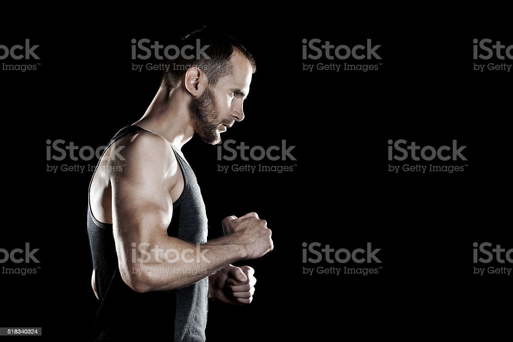 muscular man,  clasps hands in  fist, black background, place for stock photo
