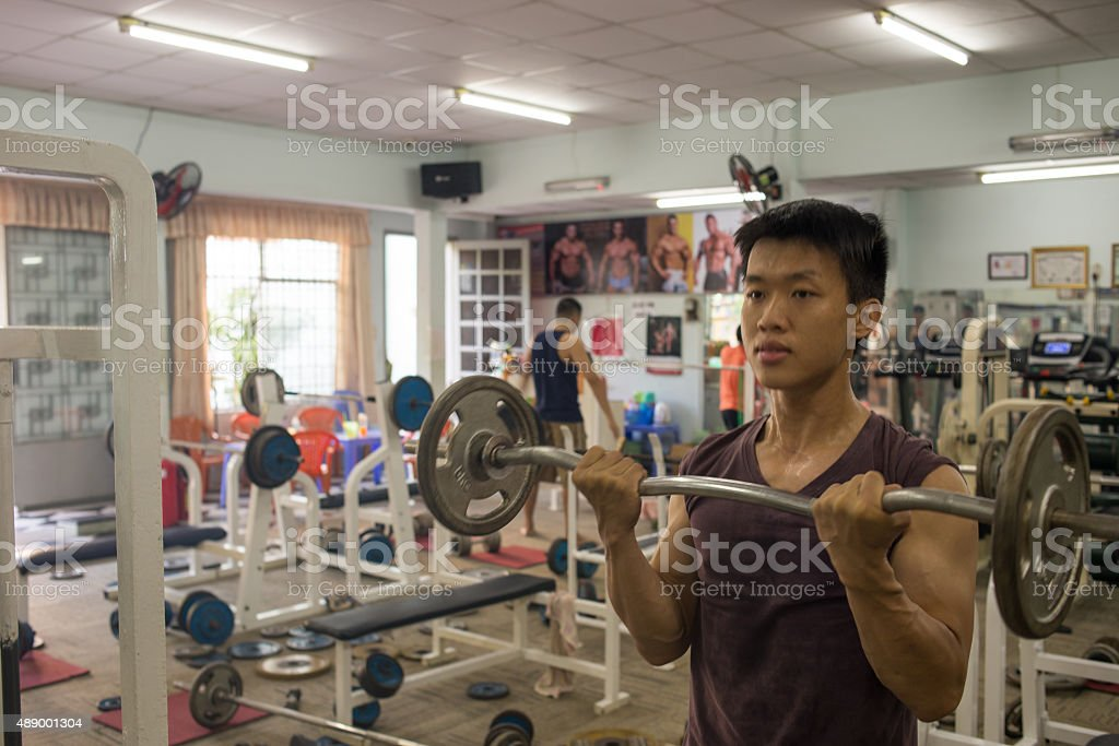 Muscular man doing barbell exercise stock photo