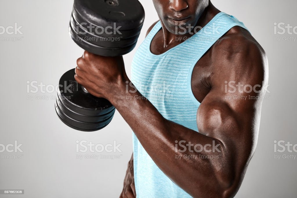 Muscular man doing biceps curl with dumbbell stock photo