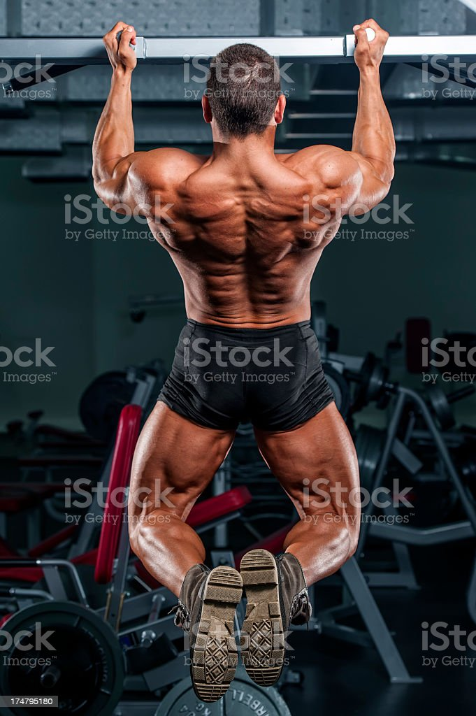 Muscular man doing chin-ups at the gym royalty-free stock photo