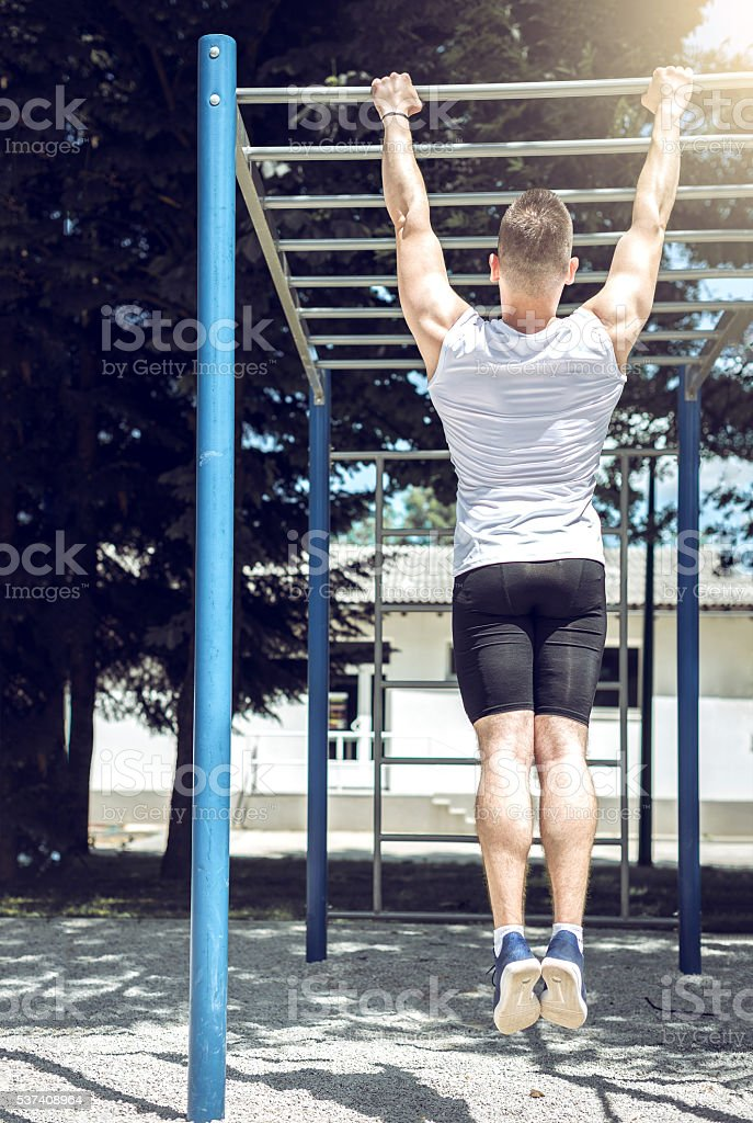 Muscular man doing pull-ups exercise outdoors. stock photo