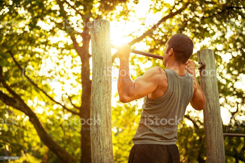Muscular man doing pull-ups stock photo