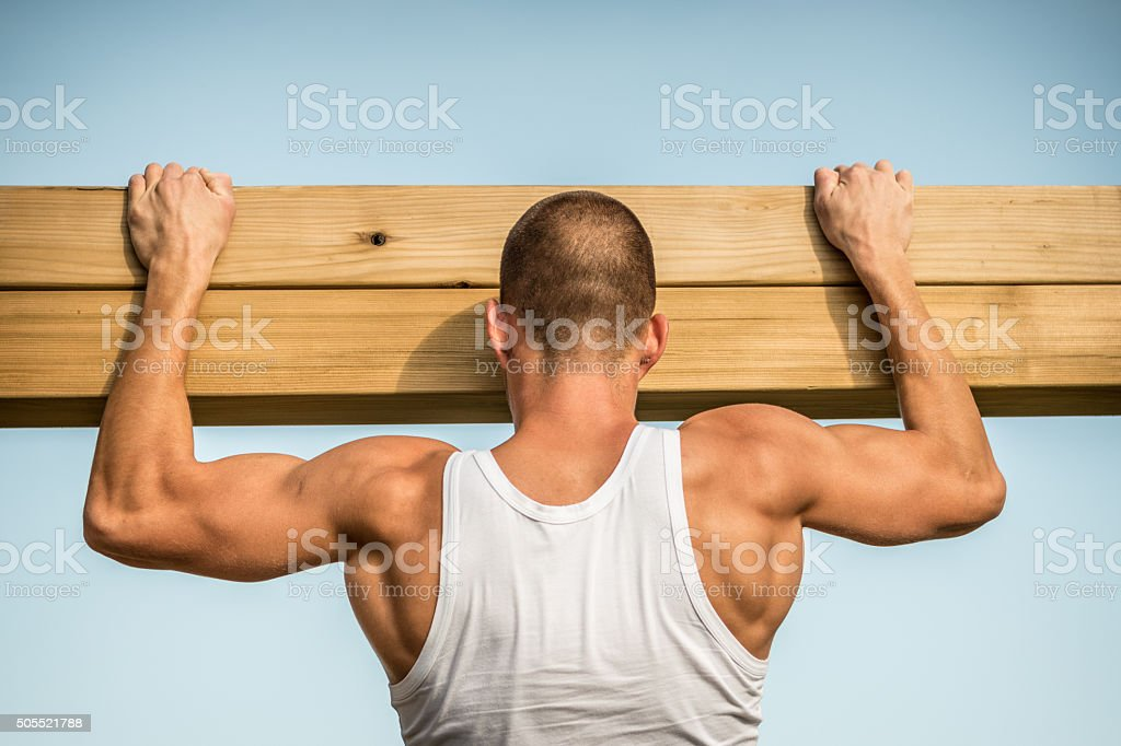 Muscular man doing pull-ups stock photo