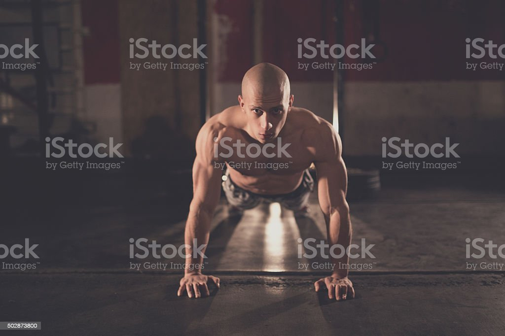 Muscular man doing push ups in grungy gym stock photo