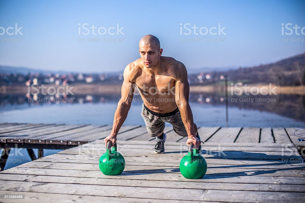 Muscular man doing push ups in nature stock photo