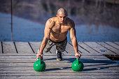 Muscular man doing push ups in nature