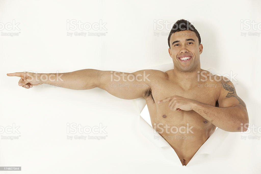 Muscular man emerging from a hole of paper royalty-free stock photo