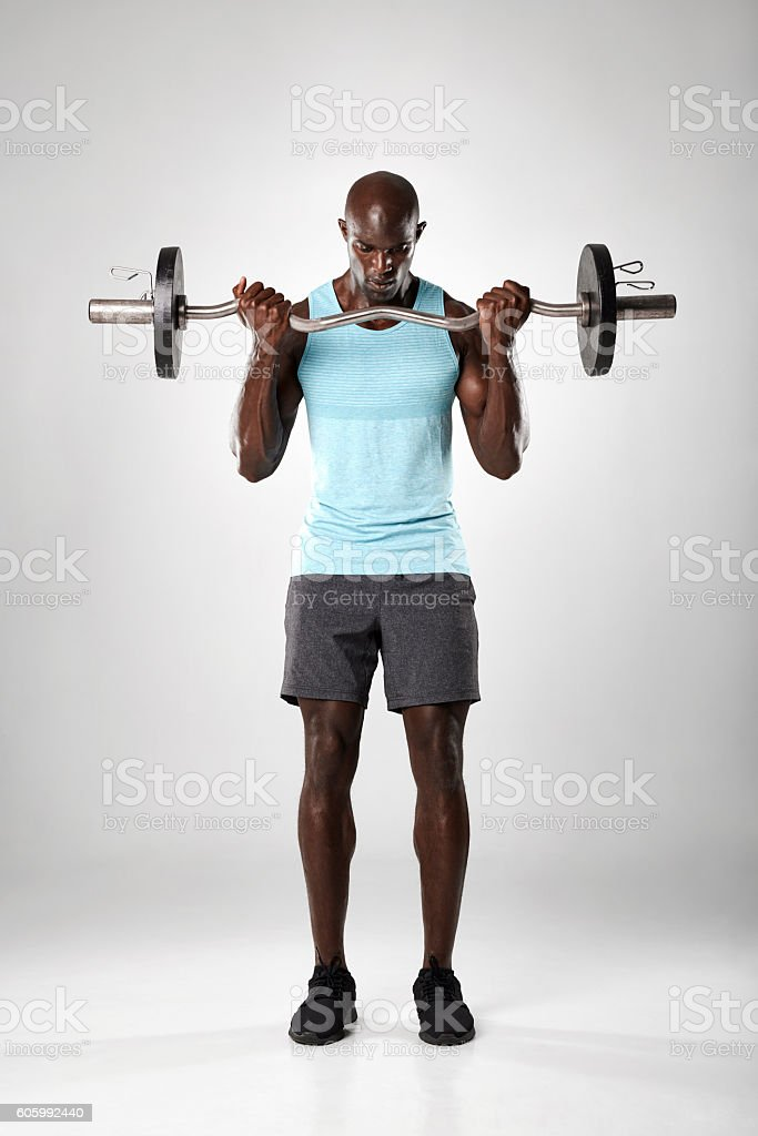 Muscular man exercising with barbell stock photo