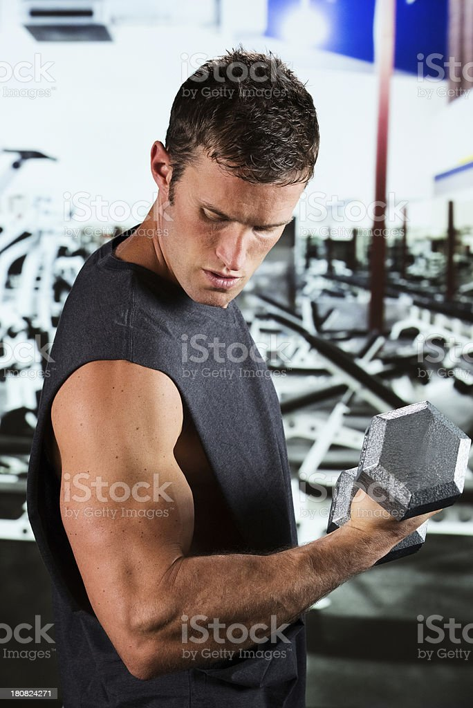 Muscular man exercising with dumbbell in a gym royalty-free stock photo