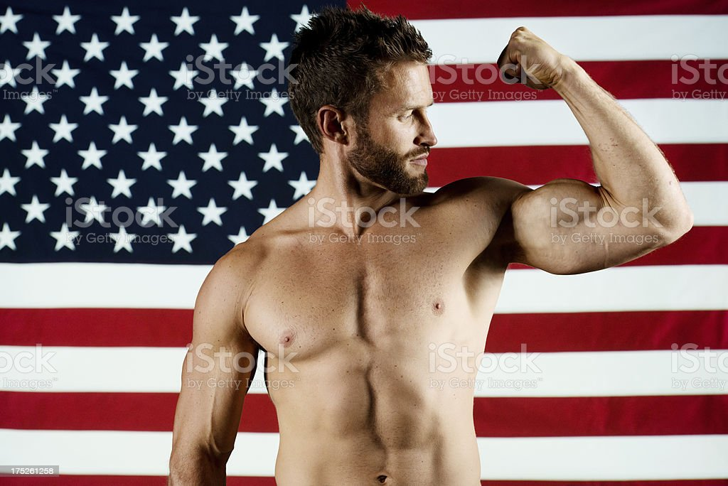 Muscular man flexing his muscles in front of American flag royalty-free stock photo