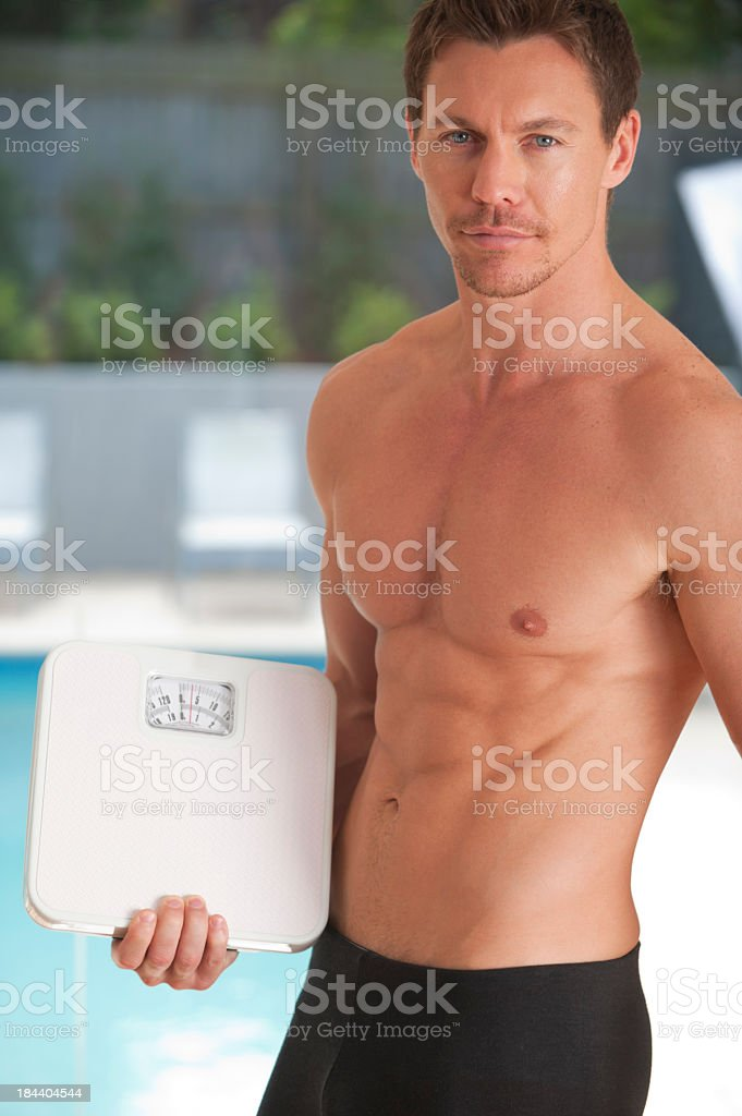 Muscular man holding bathroom scales royalty-free stock photo
