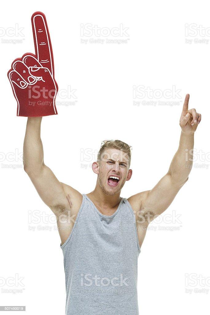 Muscular man holding foam finger & cheering stock photo
