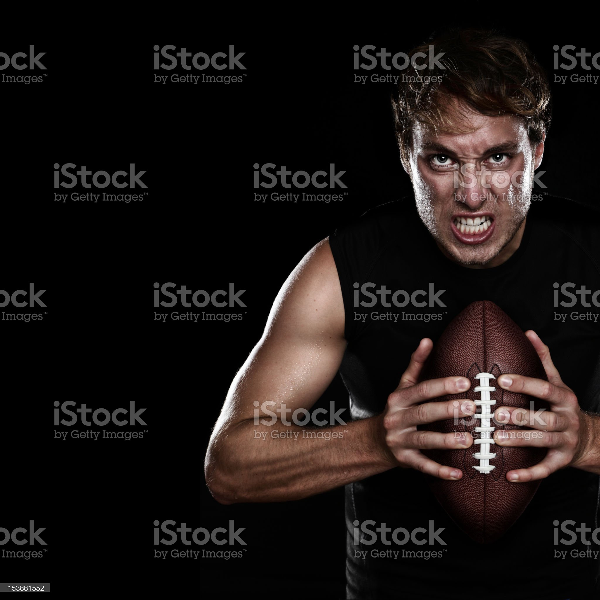 Muscular man holding football against black background royalty-free stock photo