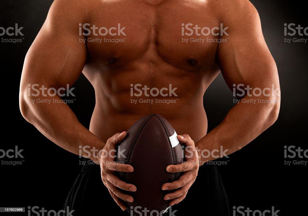 Muscular man holding football royalty-free stock photo