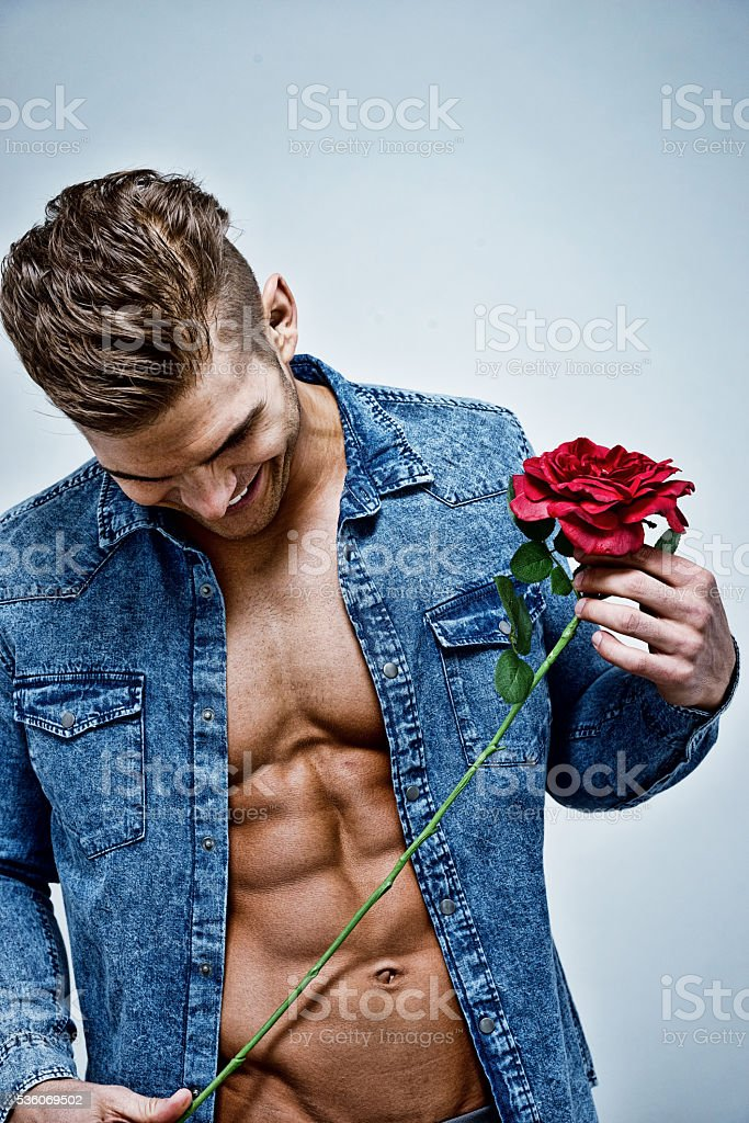 Muscular man holding rose stock photo
