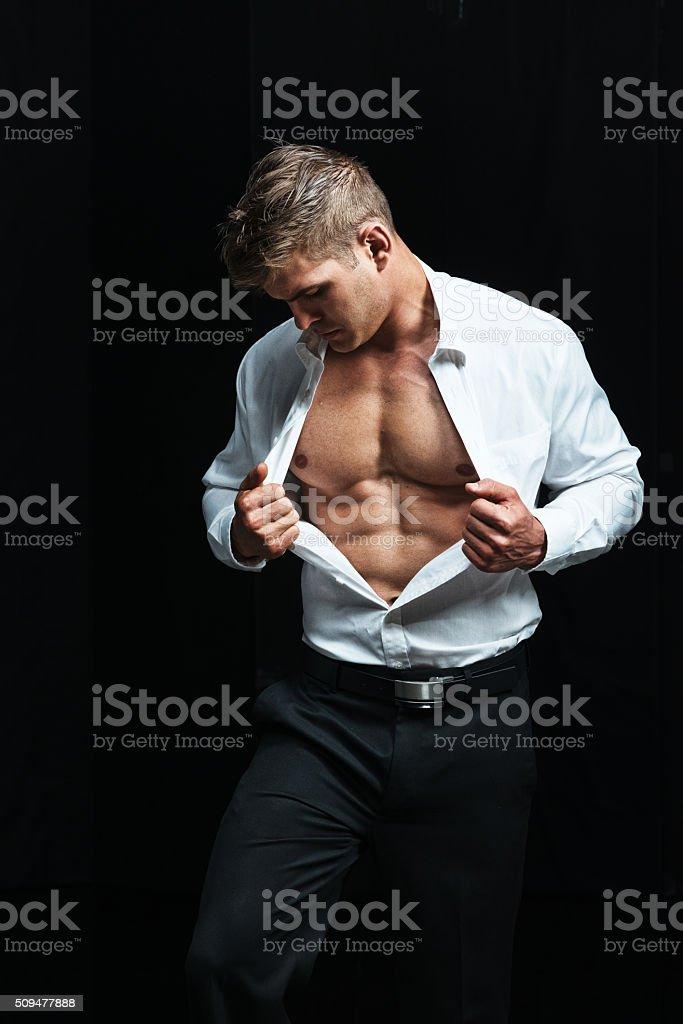 Muscular man holding shirt stock photo