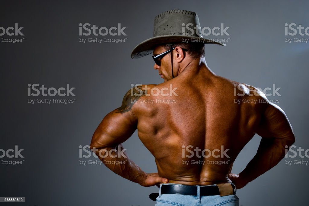 Muscular man in a cowboy hat and sunglasses stock photo
