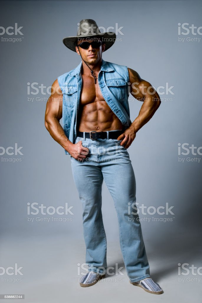 Muscular man in a cowboy hat stock photo