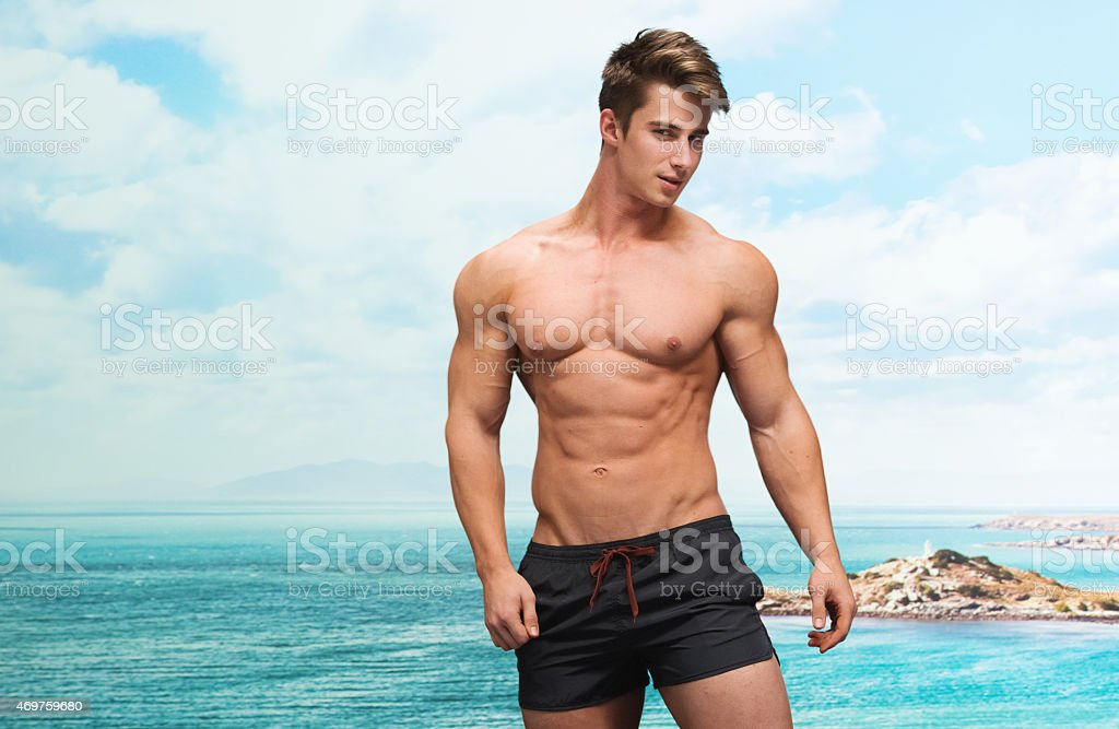 Muscular man in front of beach stock photo