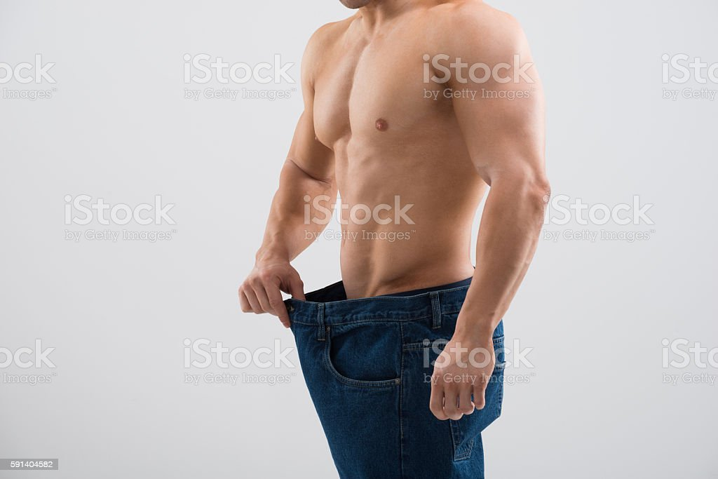 Muscular Man In Old Jeans Showing Weight Loss stock photo