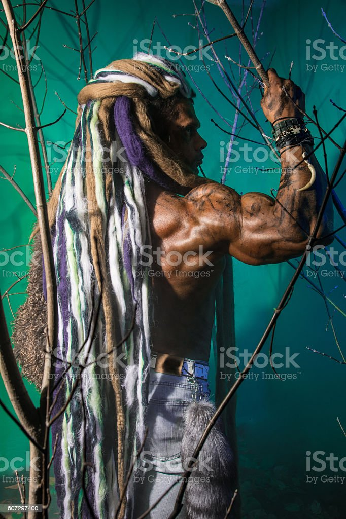 Muscular man in profile with dreadlocks in the forest stock photo