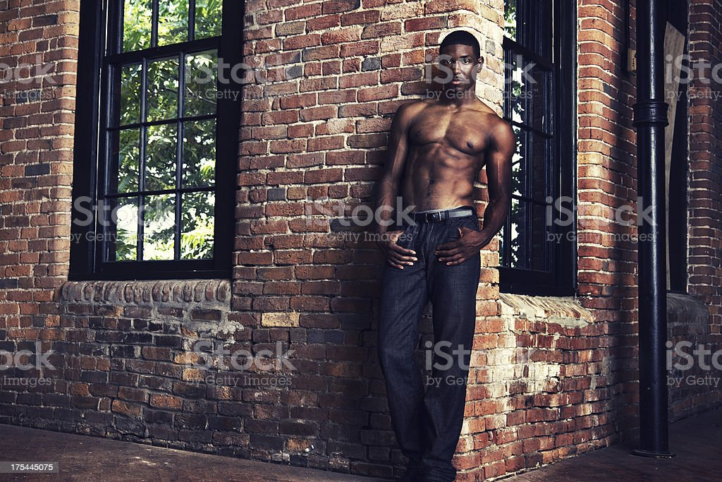 Muscular Man Leaning Against Brick Wall stock photo