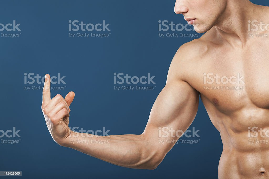 Muscular man pointing at copy-space royalty-free stock photo