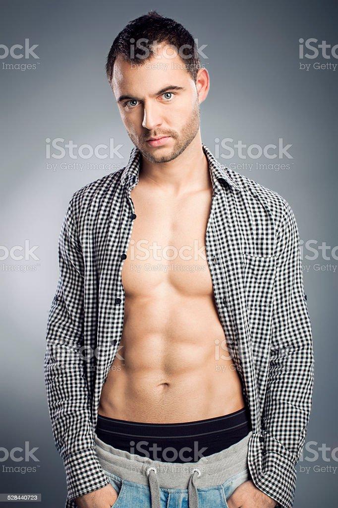 Muscular man posing in unbuttoned shirt stock photo